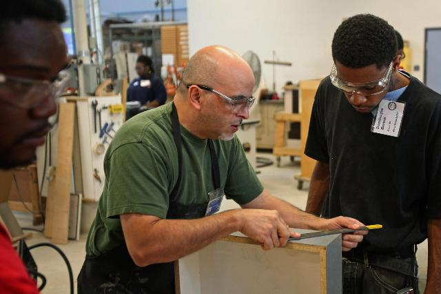 Image: Instructor helps a student participating in a woodworking manufacturing training program in Chicago, Illinois, U.S. Photographer: Tim Boyle/Bloomberg Charlie Negron